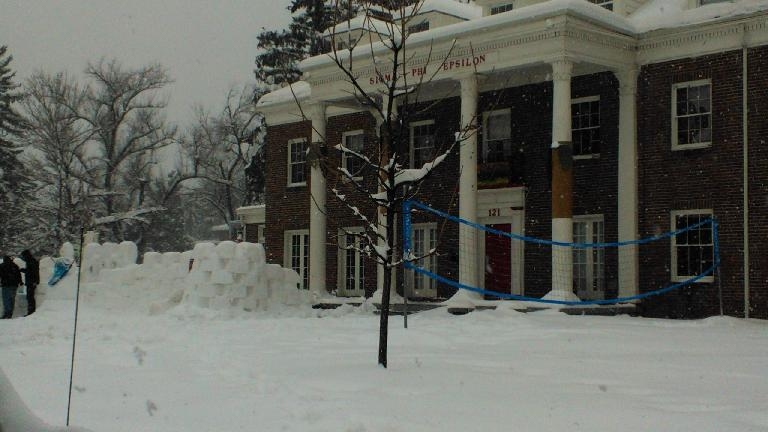 Some folks were building a wall out of snow bricks by this snowman in front of this fraternity. (April 17, 2013)
