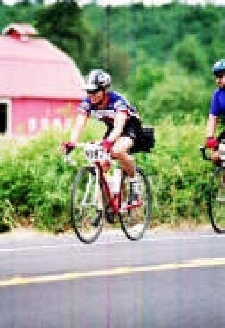 [Day 1, mile unknown] Felix Wong cruising by a farm with Mike right behind. Photo: MarathonFoto.com. (July 12, 2003)