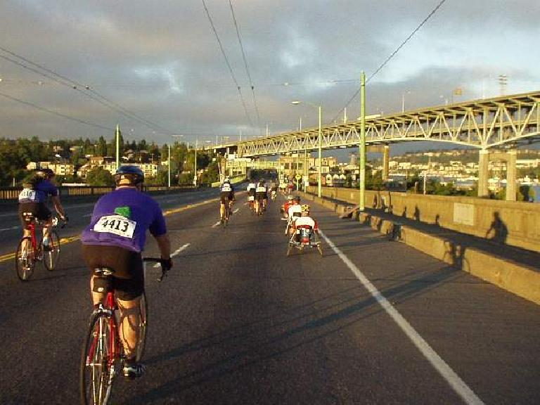 [Day 1, Mile 1.4, 6:04 a.m.] Heading over a bridge in downtown Seattle, in which a lane was closed off for us cyclists. (July 12, 2003)