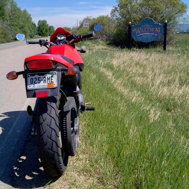 Felix Wong's red 2003 Buell Blast in front of a sign in Walden, Colorado.