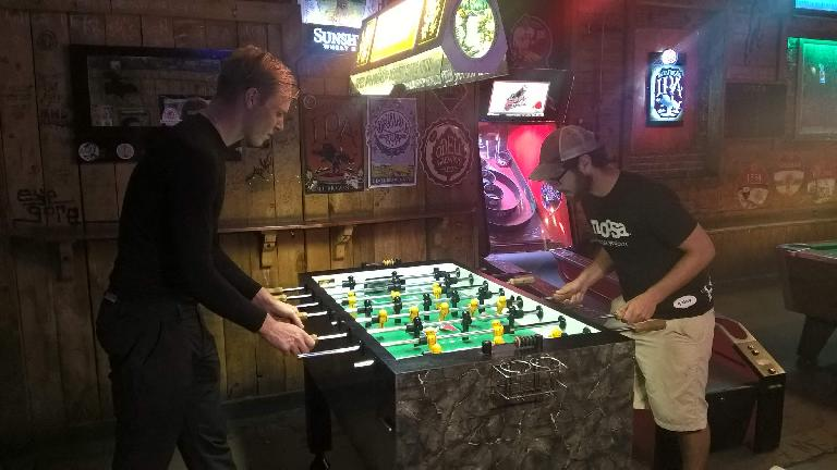 Michael Wacker and Adam Kazilsky---two veterans of the Trans Am Bike Race---playing foosball at the Trail Head in Fort Collins, Colorado. (June 16, 2016)