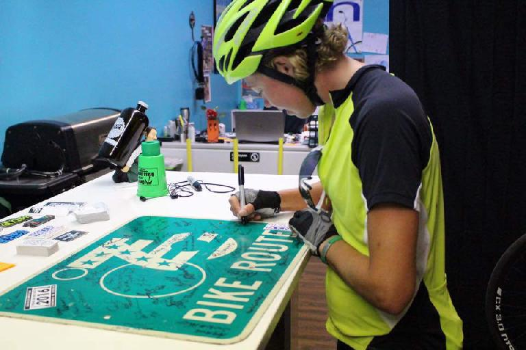 Jill Stetter signing a Bike Route sign at Newton Bike Shop in Newton, Kansas. Photo: James Barringer. (June 22, 2016)