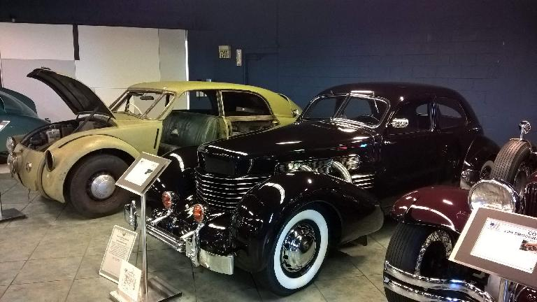 A black 1937 Cord 812 front wheel drive car with supercharger and rectractable headlights in the front fenders.