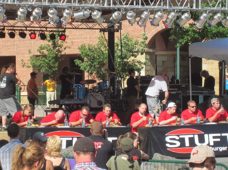 """There were nine participants in the 3-lb hamburger eating contest, including one girl (""""Beef Master"""").  The guy at the very right dominated, finishing his burger in five minutes."""