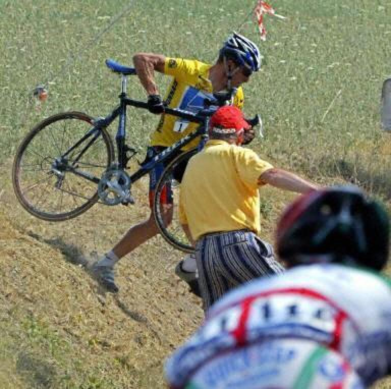 "Armstrong cutting across a field with his Trek Madone 5.9 (with aero ""shark fin"" on the seat tube) shortly after Joseba Beloki crashed in the 2003 Tour de France.  Lance hardly used that bike and seemed to prefer the Trek 5900 SL. Photo: weblogscltv.com."