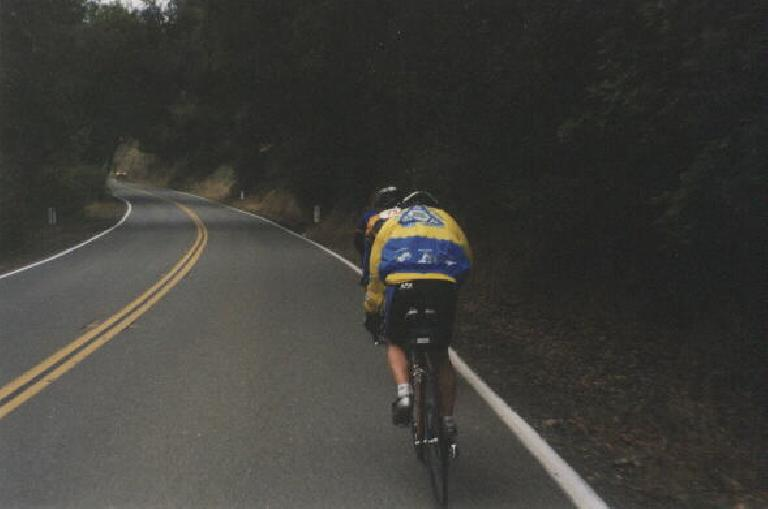Harry Gretzke wearing yellow and blue Tri-City Triathlon Club windbreaker and riding up a hill behind another cyclist.
