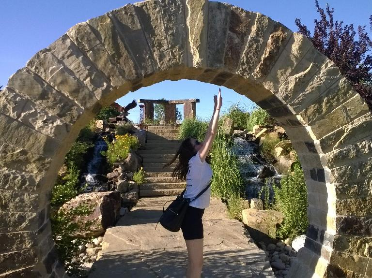 Maureen reaching for the top of the arch at The Rock Garden.