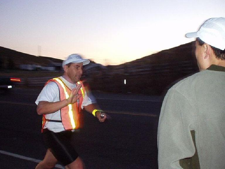 6:36pm, Mile 42: Manuel midway through his 7.4-mile leg with Everitt looking on.  Note that he is going so fast, the rest of the picture is a blur.