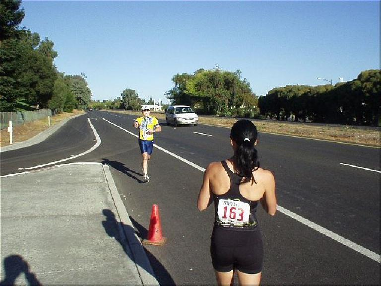 [Mile 149, 20:37 elasped, 9:07 a.m.] Lisa awaits a handoff from Phil after his third and last leg along Foothill Blvd in Palo Alto. (October 12, 2003)