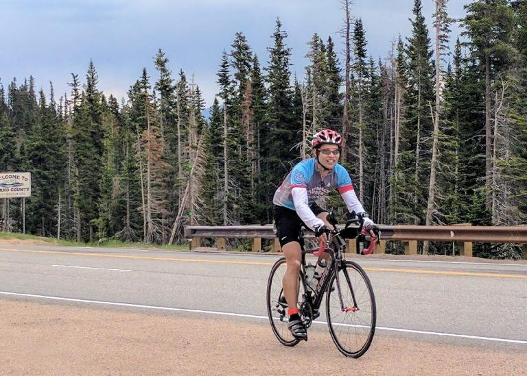 Felix Wong riding a black 2010 Litespeed Archon C2 over the summit of Berthoud Pass, Colorado.