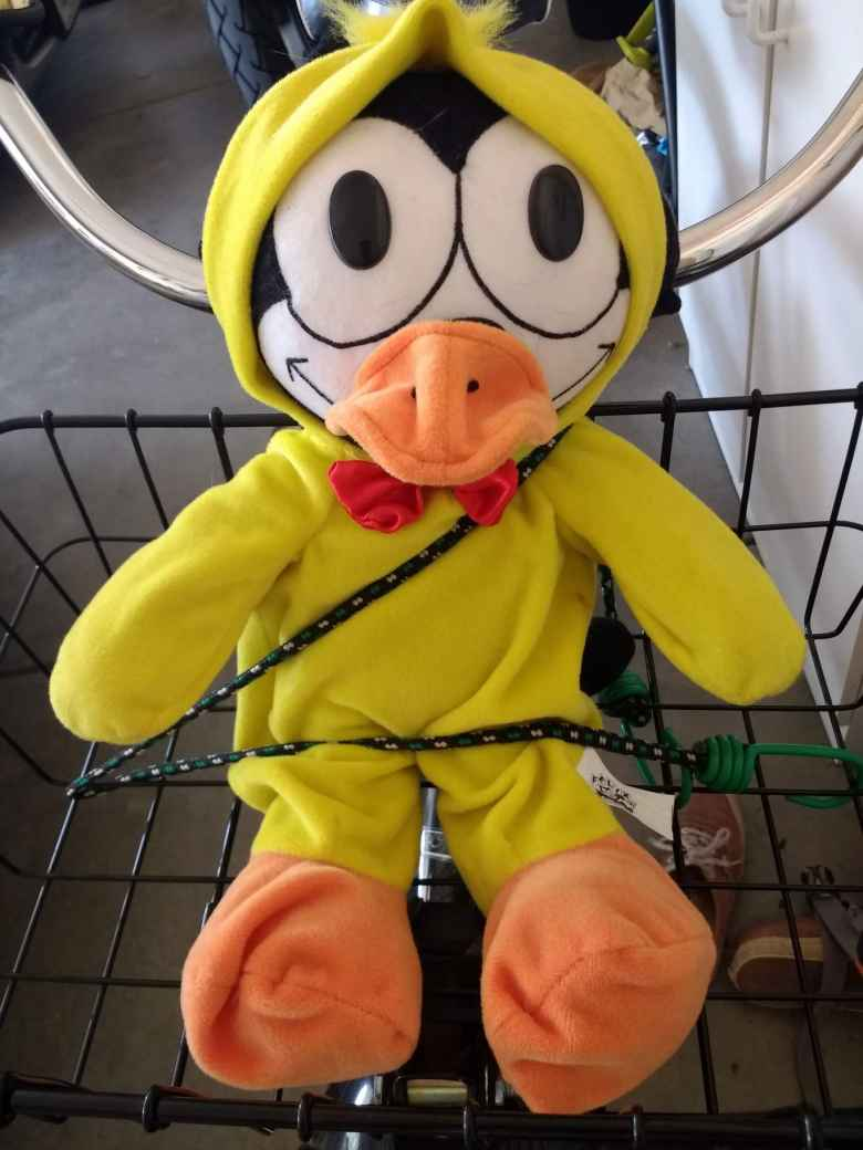Felix the Cat wearing a yellow duck costume, bungee cord seat belt