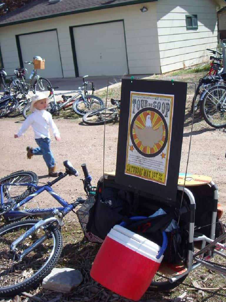 A boy running by bikes and the Tour de Coop sign.