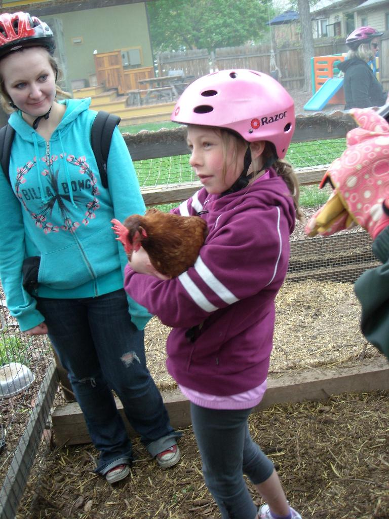 Girl holding a chicken.