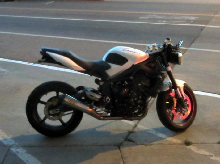 A Triumph Street Triple with 3-in-1 exhaust, and possibly some fairings (and the rear fender) removed.