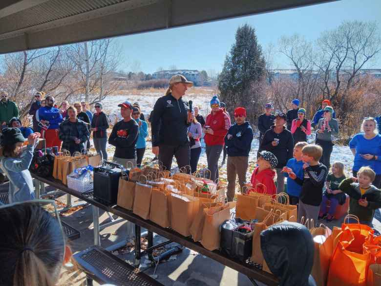 Melody, the organizer of the Turkey-Donut Predict 5k, announcing the winners of what must have been over 100 raffle prizes.