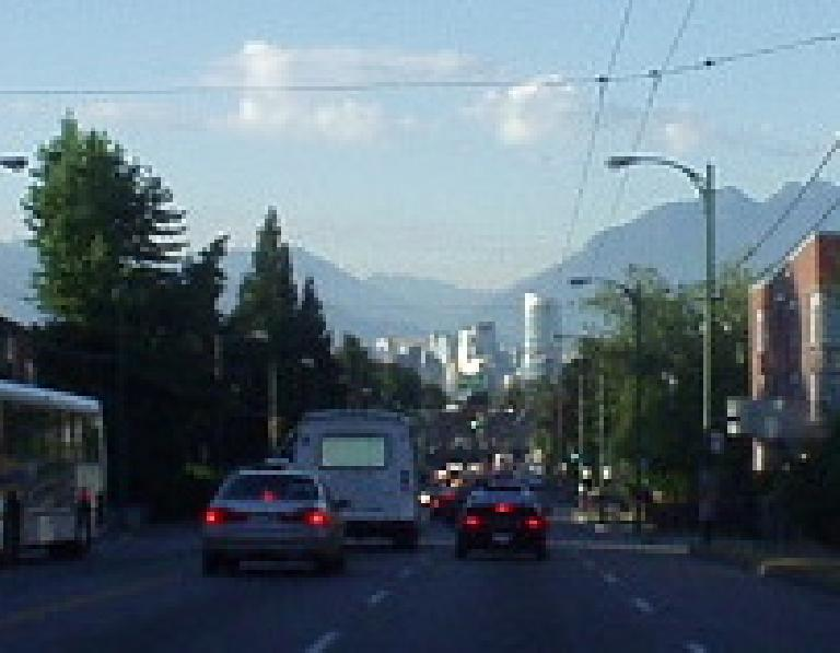 The modern, glassy Vancouver skyline is dwarfed by the granite mountains in the backdrop.