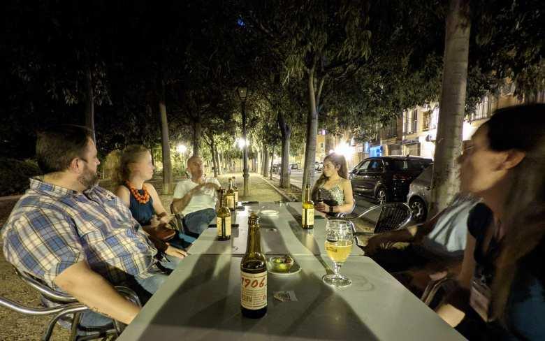 Victor, Lydia, Angel, Melissa, Ismael, and Nieves enjoying bottles of 1906 at night in Aranjuez.