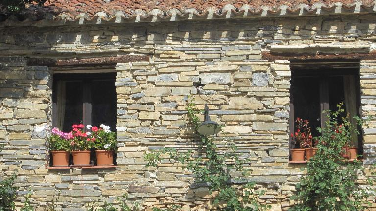 Flowers in windows in the rustic buildings in Valdelavilla. (August 26, 2013)