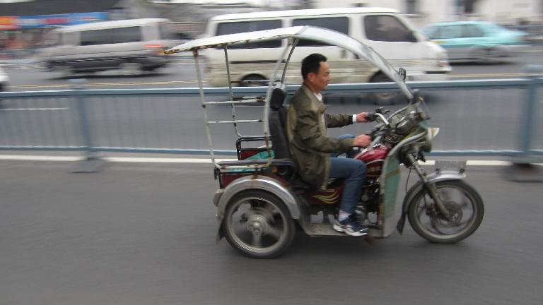 Three-wheeled motorized vehicle with roof in Suzhou. (May 17, 2014)