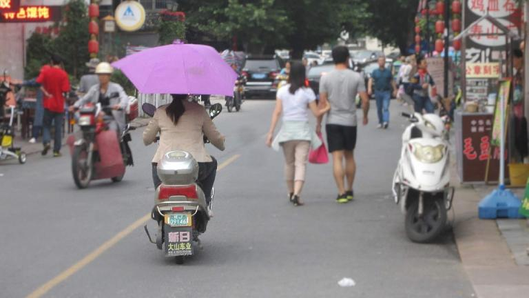 Woman driving a motorbike with a fixed purple umbrella in an area near Tunxi Ancient Street of Huangshan City. (May 20, 2014)