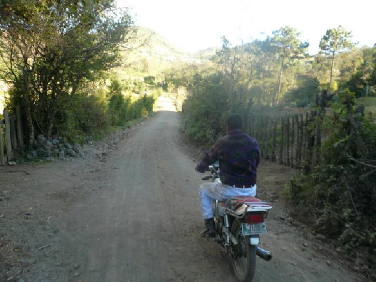 Carlos on his Suzuki motorcycle on some backroads near San Andres Itzapa.  I road on the back and unfortunately we had just taken a spill before I took this photo. (January 3, 2011)