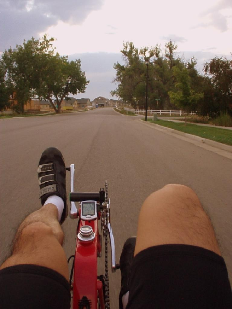 view of legs pedaling a red Reynolds Wishbone recumbent down the street towards some trees with speedometer reading 16.4 MPH