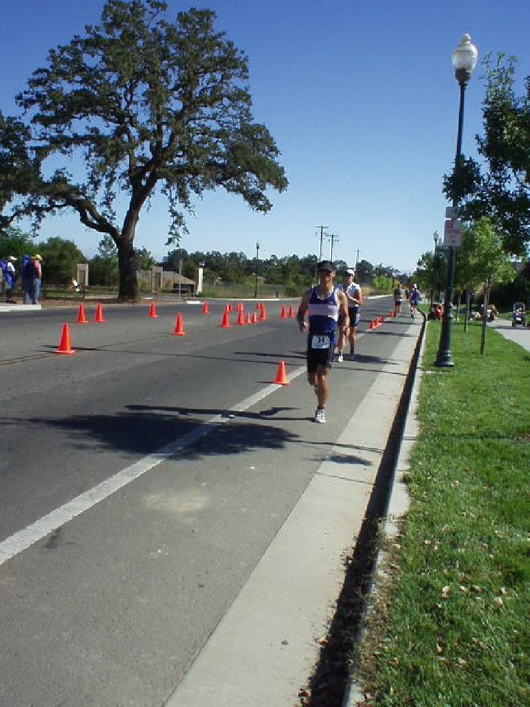 [Run Mile 8.6, 9:50:xx elapsed] Energy conservation on the bike paid off!  Here I am after the first loop (of three), able to (slowly but steadily) run the entire marathon without walking. Photo: Sharon Schneckenberger.