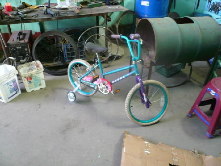 This bike was to be a gift for a boy, so I swapped its original pink seat for a black one to make it less girly.  Also added training wheels. (January 4, 2011)