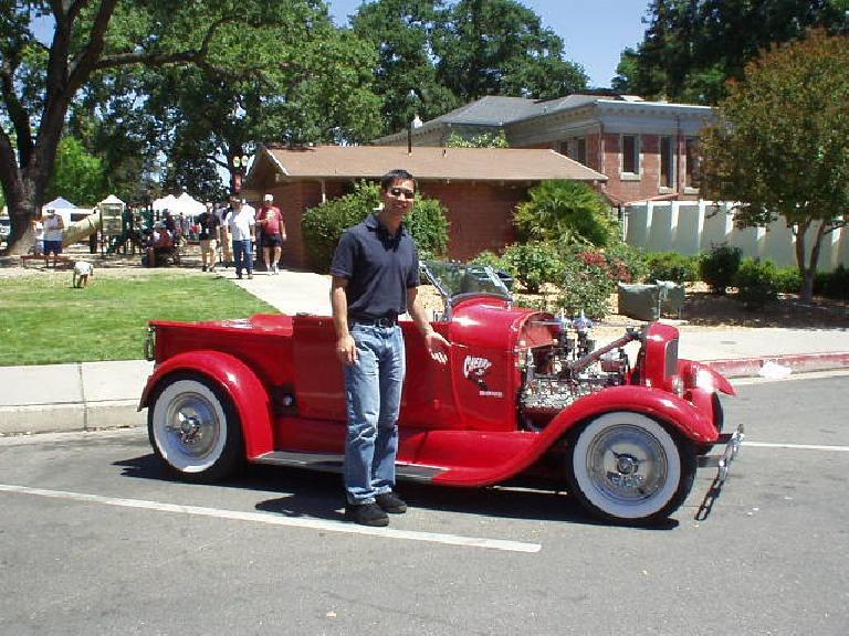 Felix Wong next to a fire-engine-red truck that had Felix Wong the Cat painted on it.