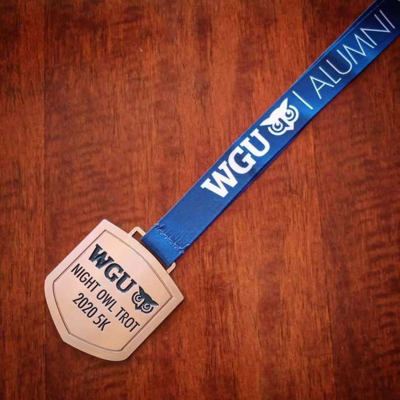 gold-colored medal that says WGU Night Owl Trot 2020 5K attached to blue lanyard that says WGU Alumni