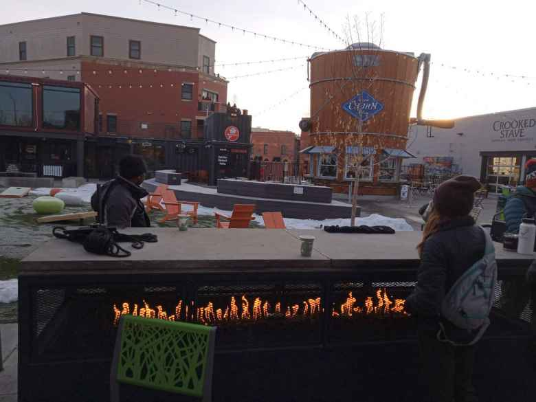 Brooke warming up by the fire at the Exchange in Old Town Fort Collins during Winter Bike to Work Day.