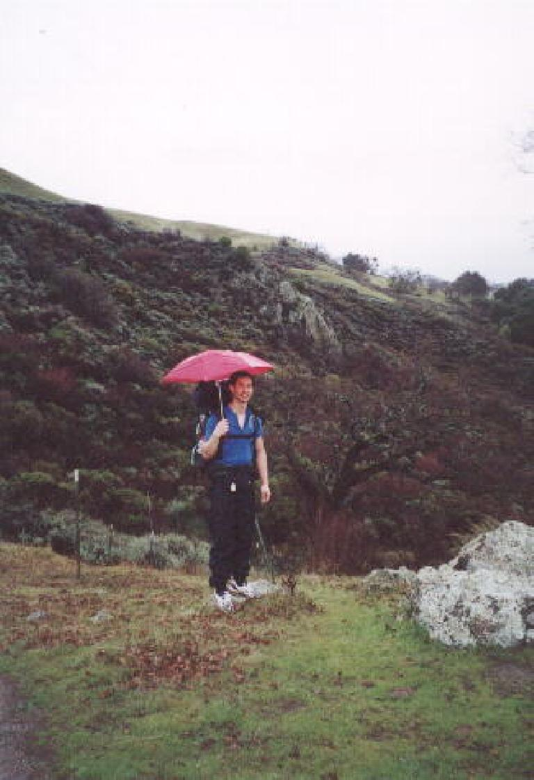 [Ohlone Wilderness Trail, Jan 2002] Felix Wong experimenting with using an umbrella during the 15-mile rain hike into camp.  It worked well! Photo: Sarah Toas. (January 26, 2002)