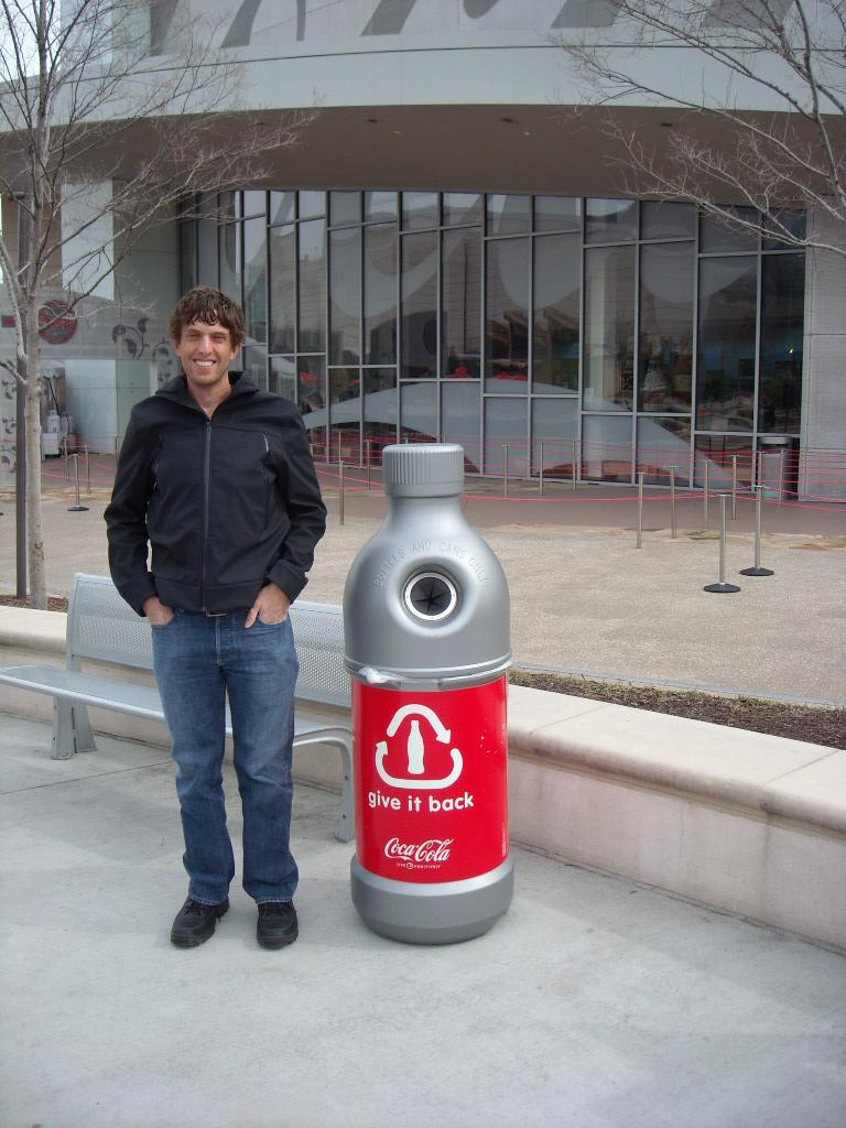 Dan next to a bottle-shapped recycling repository.