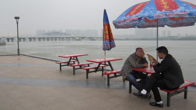 Two men talking by Taihu Lake (a.k.a. Lake Tai) at Lihu Park.